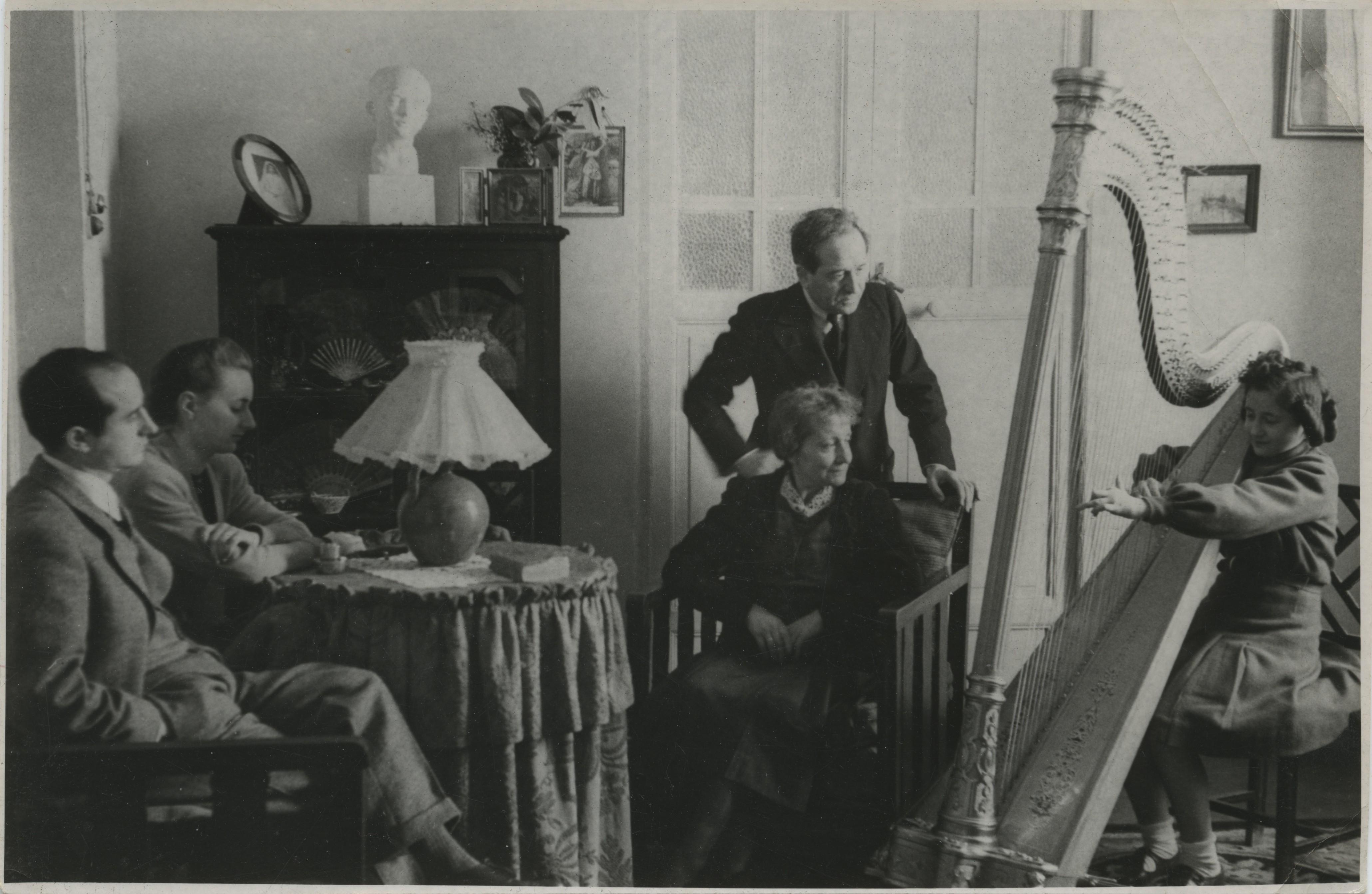 1942.2. JHC con su mujer, Ana, sus padres Jacinto y Lola y su hermana Mari Lola tocando el arpa, en el salón de la Plaza de Oriente, 6, Madrid, 1942