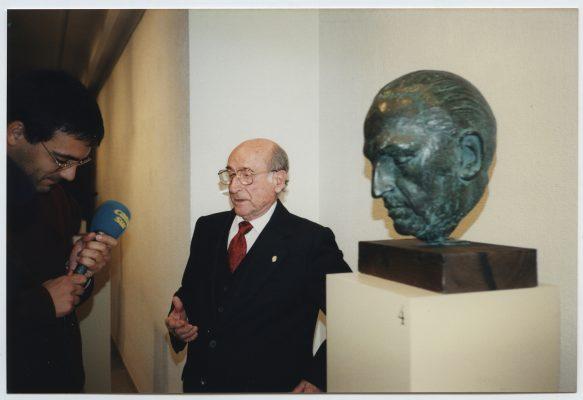 1996.8. JHC, junto a la Cabeza del doctor Gregorio Marañón, con un periodista de Canal Sur en la Inauguración de la Exposición Antológica en Granada, Sala Triunfo, 5 de noviembre de 1996